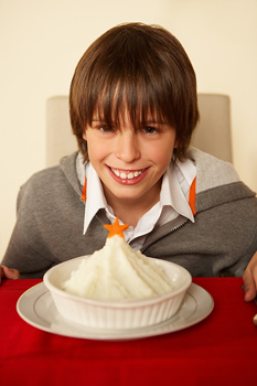 Smiling boy posing at table with mashed potatoes
