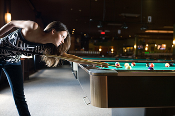 Woman playing game of billiards