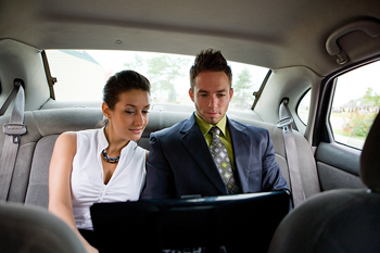 Businesspeople in taxi with laptop computer