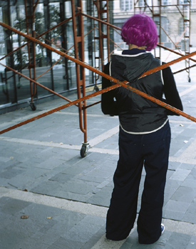 Woman with purple hair standing against scaffolding