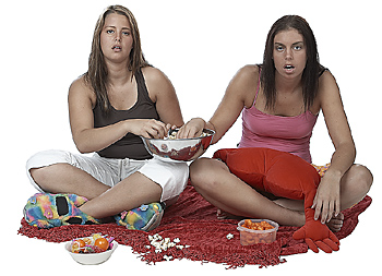 Teen Girls Sharing Snacks and Watching TV