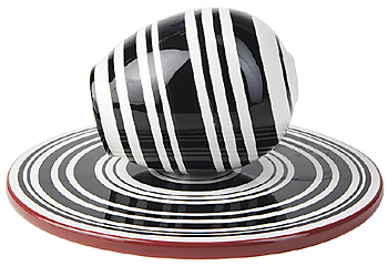 Black and white striped shaker on saucer