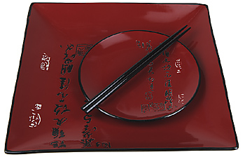 Chopsticks atop round and square Asian plates