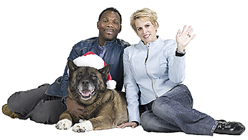 Couple posing with dog in Santa hat