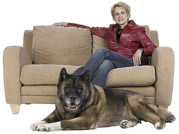 Woman posing on couch with dog on floor
