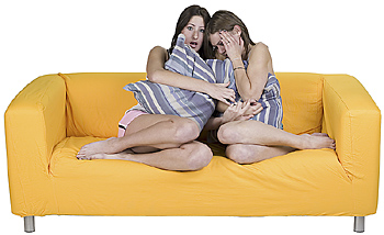 Two women on sofa scared