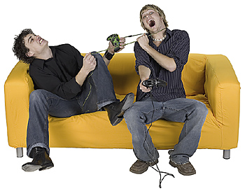 Two men on sofa playing video game