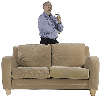 Man standing behind couch in thoughtful pose