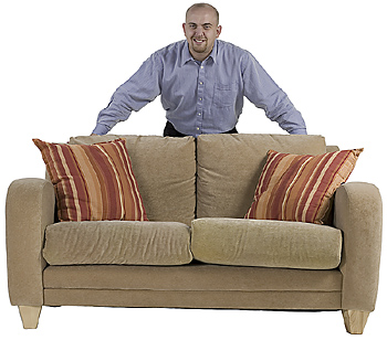 Man posing behind couch