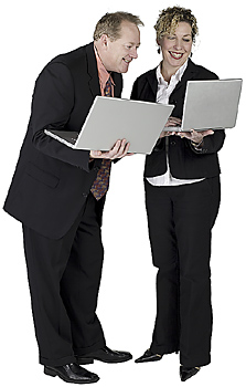 Businessman and businesswoman using laptops