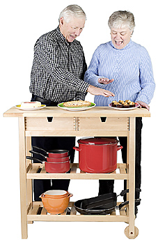 Senior couple standing with kitchen cart