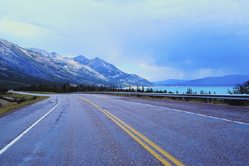 Highway by lake and mountains