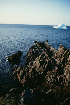 Rock formation with iceberg in ocean