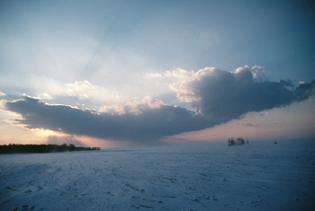Clouds over snowy field at dawn, Quebec, Canada