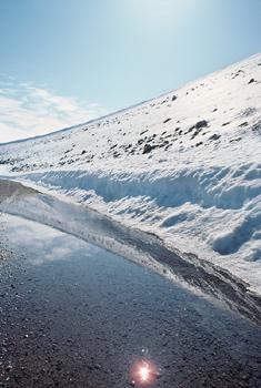 Snowy hill by sheet of ice, James Bay, Canada