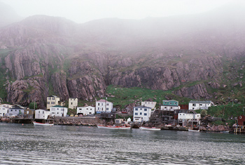 Houses along riverbank and rocky cliff