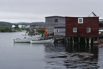 Boats by houses on stilts in water