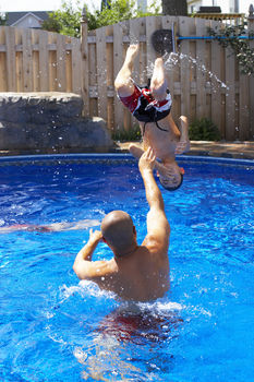 Father playing with son in swimming pool