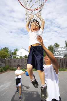 Father helping son reach top of basketball hoop