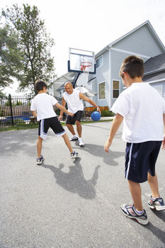 Father playing game of basketball with sons