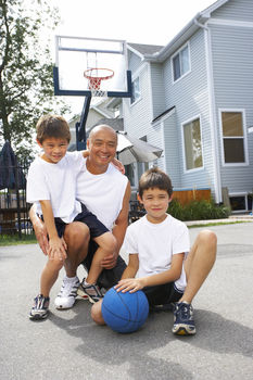 Father posing with sons at basketball court