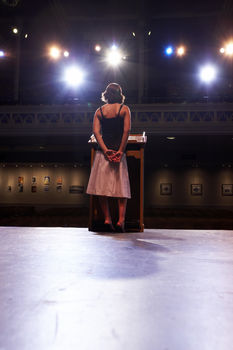 Teenage girl at podium under stage lights