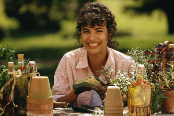 Smiling woman posing by potted plants