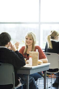 Teenager girl talking to friend in high school cafeteria