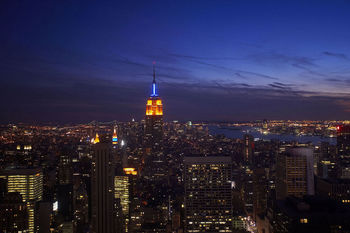 Top of the Empire State Building illuminated at night above New York City