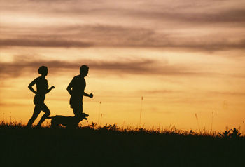 Silhouettes of runners at sunset
