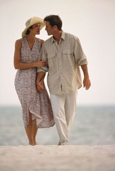 Couple holding hands, strolling on beach