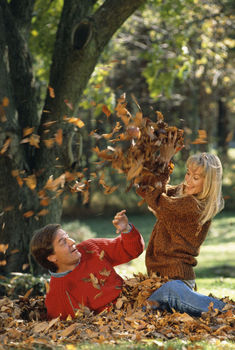 Couple playing outdoors in autumn leaves