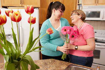 Woman giving mother flowers
