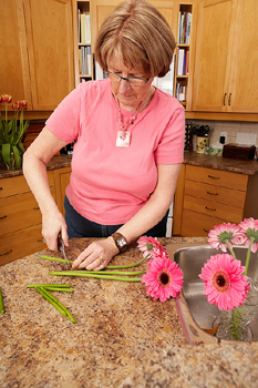 Woman cutting stems of flowers