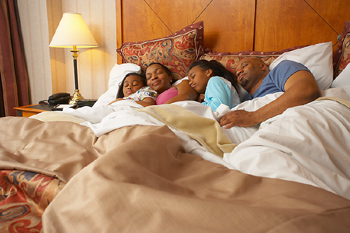 Family asleep in hotel room