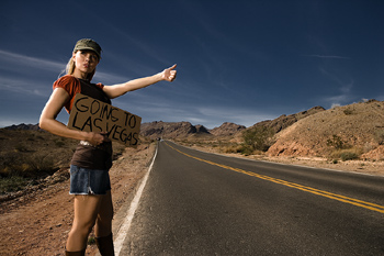 Woman with sign hitchhiking to Las Vegas