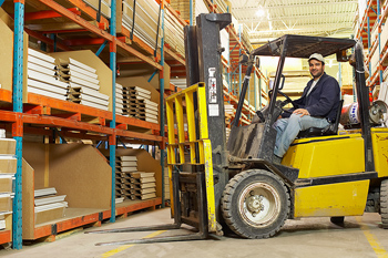 Warehouse worker posing in forklift