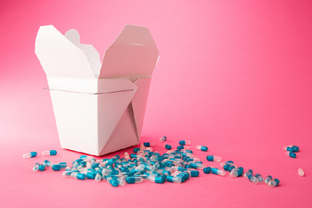 Open take-out box with scattered capsules