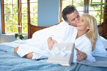 Husband giving woman present in bed