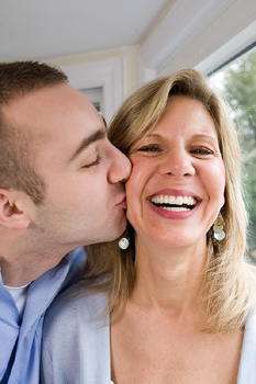 Adult son kissing mother at home