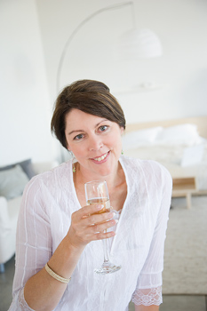 Smiling woman at home with glass of champagne
