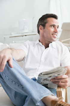 Smiling man in chair with newspaper at home