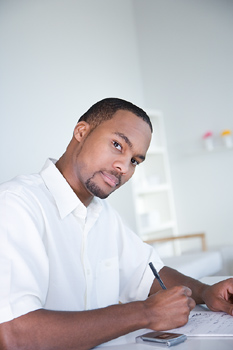 Man writing at table or counter in office