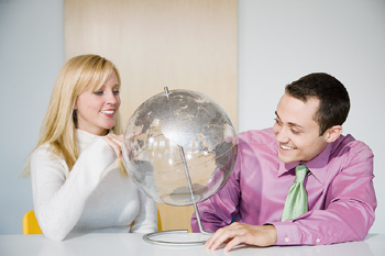Man and woman looking at globe on table