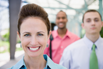 Smiling woman posing outdoors, with others