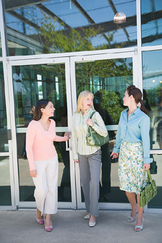 Three women standing outside building