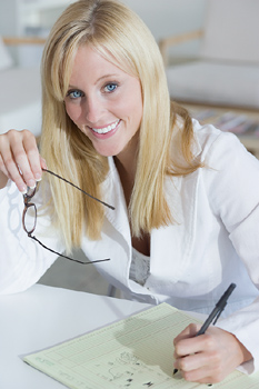Smiling woman at desk writing on paper