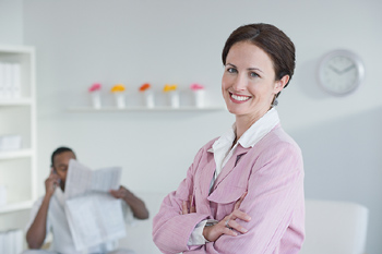 Businesswoman posing in office with others