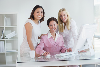 Three women posing together at desk