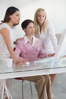 Three women working together at computer